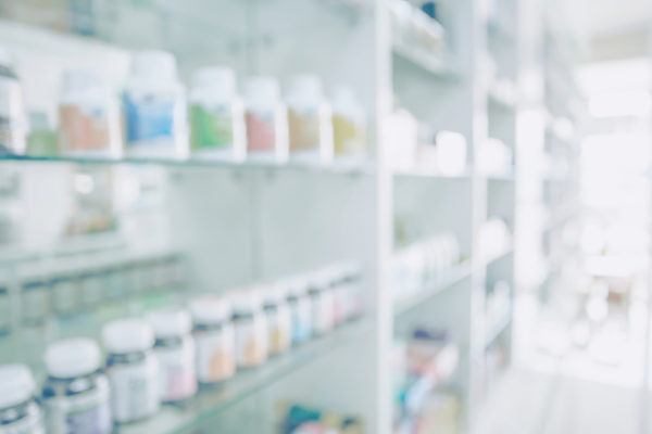 Pharmacy blurred light tone with store drugs shelves interior background